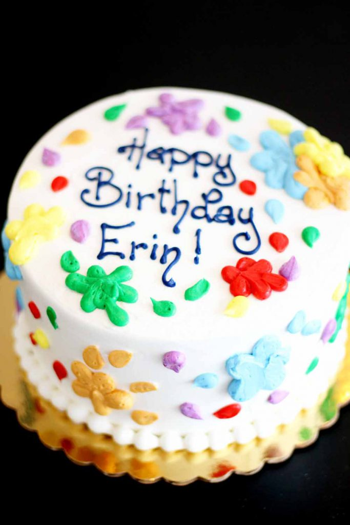 round birthday cake with buttercream paint splatters