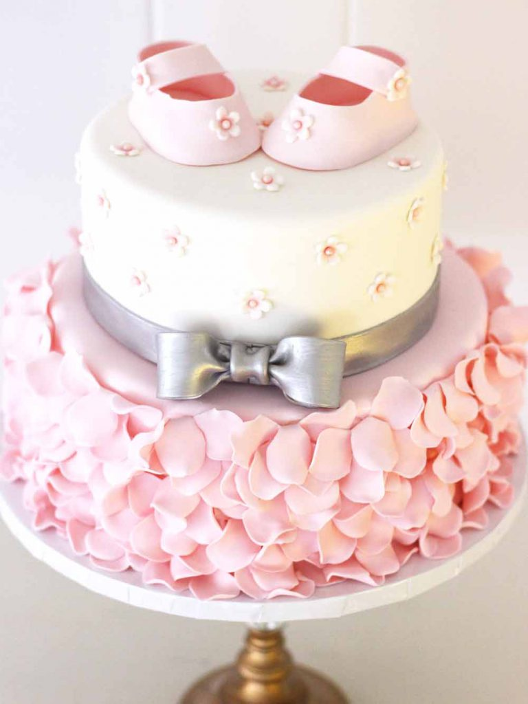 fondant baby shower cake with fondant shoes, petals, and bow in pink and silver