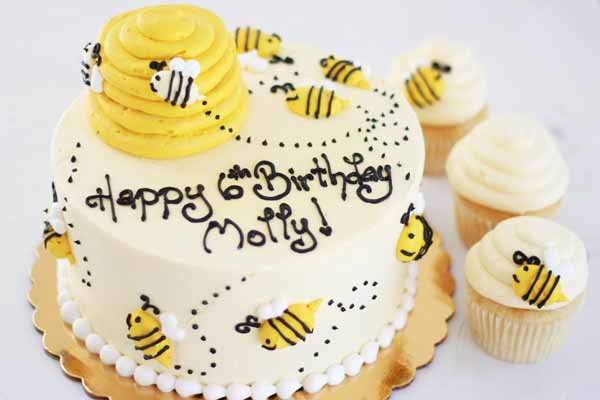 yellow bumble bee birthday cake with matching cupcakes