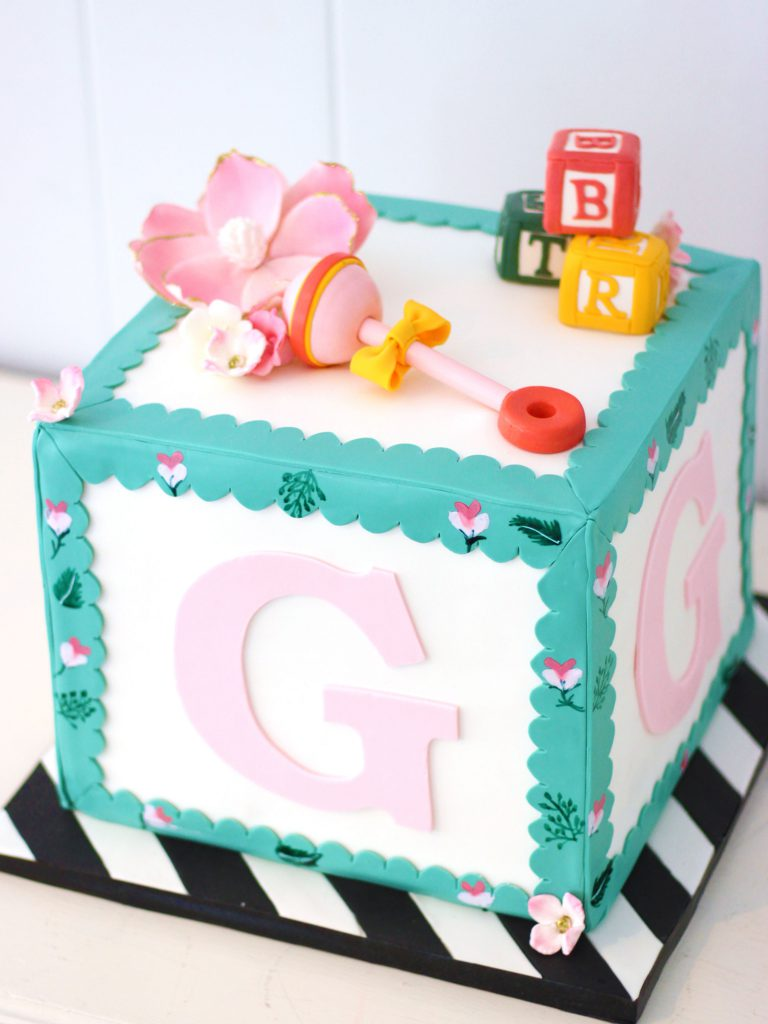 elegant baby block cake with rattle, flowers, and letter blocks