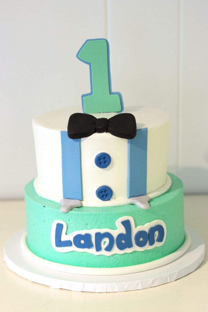 first birthday cake with suspenders, bowtie, and buttons in blue and green