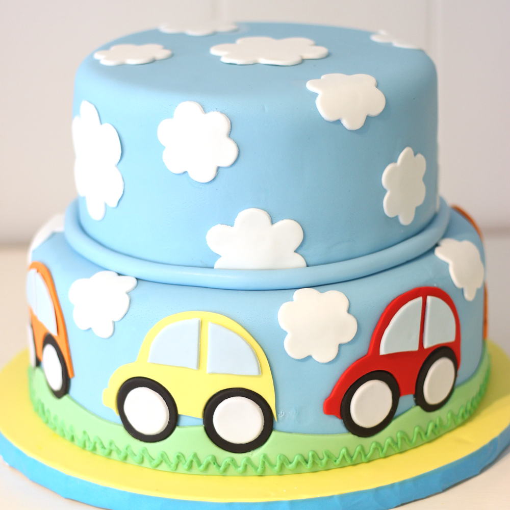 Cars, grass, and clouds in the sky fondant custom cake