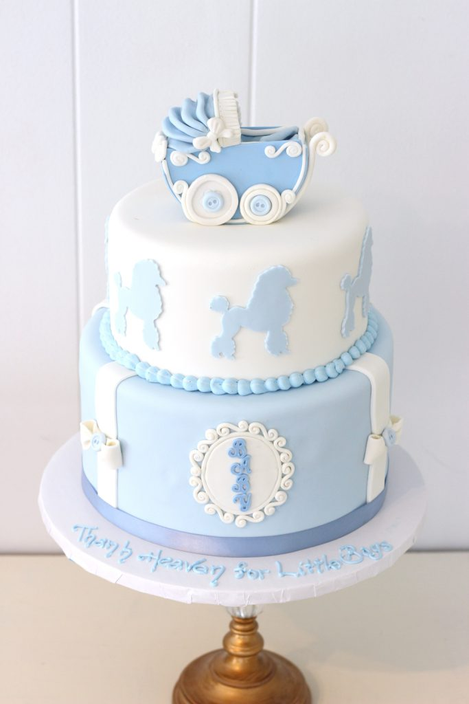 two tier fondant baby shower cake with poodle cut outs and pram